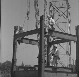Structural steel, 1968; two workers securing corners of a structure; one worker operating a crane