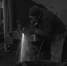 Welding, Nanaimo, 1968; man wearing protective goggles and glove welding