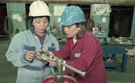 Trades discovery for women; piping/plumbing, instructor (?) demonstrating to students wearing har...