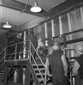 Forestry, Wood fiber BCIT tour, November 26, 1965; men wearing hard hats walking through a factor...