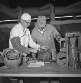 Welding, Terrace, 1968; two men standing at a table looking welding marks on an item