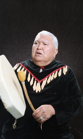 Bob George, First Nations elder, in First Nations garment playing an instrument [22 of 36 photogr...