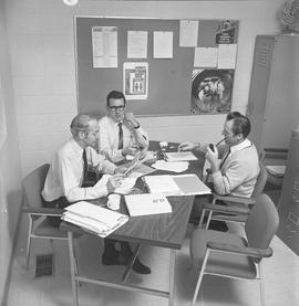 BCVS Graphic arts ; three men at a table talking [2 of 2]
