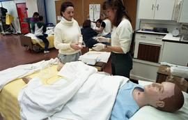 General Nursing, student and nurse with dummy patient in bed [2 of 4 photographs]