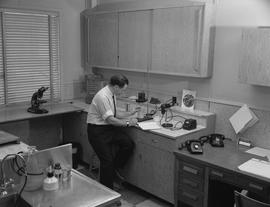 Forest Products, 1964; a man sitting at a desk in a testing lab examining a sample ; wood samples...