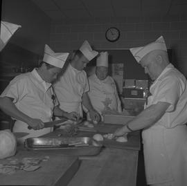Tow boat cook course; instructor watching students chopping vegetables [3 of 6]