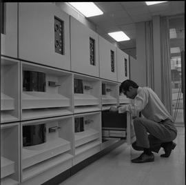 Man kneeling down and working with IBM 2501, Business Management program