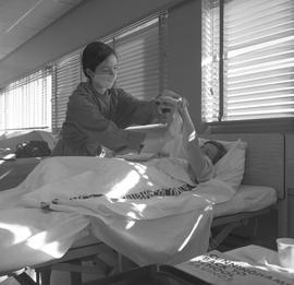 Practical nursing, Prince George, 1968; nurse wearing a face mask tending to a patient's arm