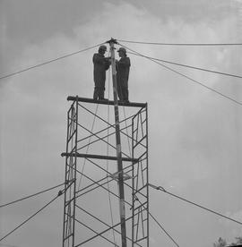 Structural steel, 1971; two men standing at the top of scaffolding attaching cabling to a pole [2...