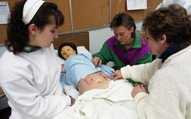 General Nursing, students and nurse examining dummy patient in a bed [3 of 5 photographs]