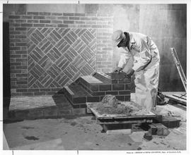 Bricklaying; a student building steps made of brick in front of a decorative brick structure ; Ph...