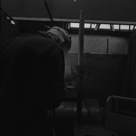 Welding, Nanaimo, 1968; man welding (back view)