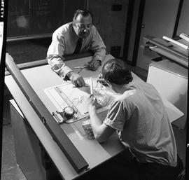 BC Vocational School drafting course ; student working on a diagram using a compass ; instructor ...
