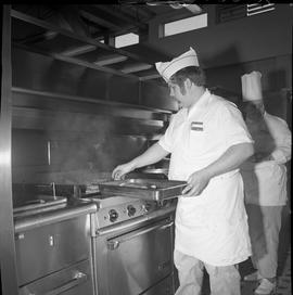 BC Vocational School Cook Training Course ; student placing meat on grill