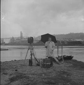 Survey, 1971; man with an umbrella standing next to surveying equipment