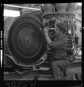 BC Vocational School; Aeronautics student kneeling and working on an aircraft engine inside the h...