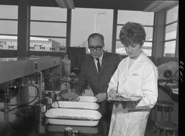 Food Processing Technology, 1966; woman in a lab coat writing notes ; man in a suit moving a dish...
