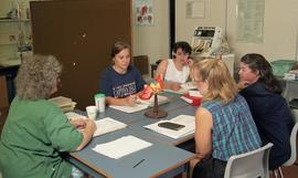 C/Care (students in action), 1993, students and nurse working at table [1 of 3 photographs]