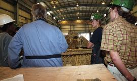 BCIT women in trades; welding, instructor leading a group of students in hard hats on a tour insi...