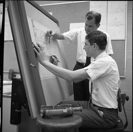 BC Vocational School drafting course ; student sitting at a drafting desk and instructor pointing...