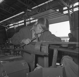 Sheet metal, 1968; student using a hammer to shape a piece of metal ; workshop in background