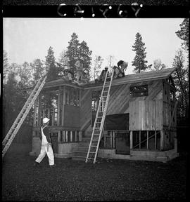 B.C. Vocational School; Carpentry Trades students roofing a small house under construction with l...