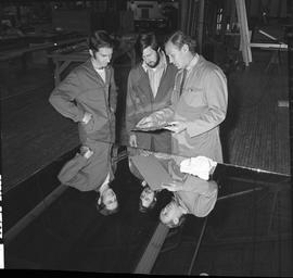 BCVS Glazier program ; three men looking at a piece of glass ; workshop in background [1 of 2]