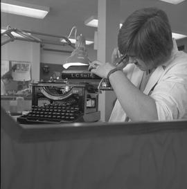 Office Machine Mechanic, 1968; man repairing the rollers on a typewriter