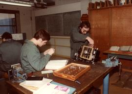 Students in workshop, textbooks, equipment, coveralls