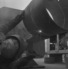 Welding, Prince George, 1968; person laying on their back welding the underside of a pipe
