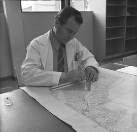 BCIT Programs Forestry Technology ; man measuring distance on a map using a ruler
