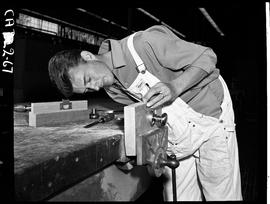 B.C. Vocational School image of a Carpentry Trades student attaching a door handle to a wood bloc...