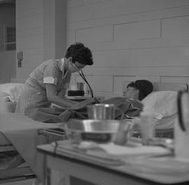 Practical nursing, Prince George, 1968; nurse wearing a face mask checking a patient's blood pres...