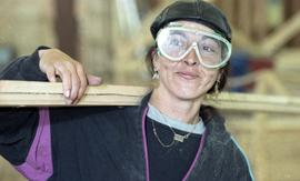 BCIT Women in Trades Training; carpentry, woman with eye protection, carrying wood [2 of 3 photog...