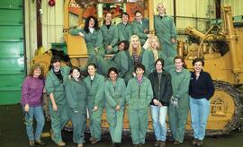 BCIT women in trades; heavy duty, students in uniforms standing in front of a bulldozer [4 of 9 p...