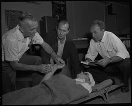 Industrial First Aid, Nanaimo; instructor showing student how to check the pulse of a man lying o...