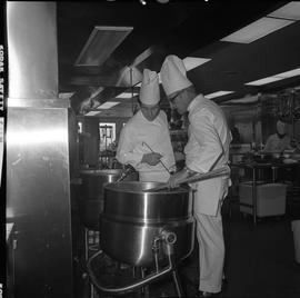 BC Vocational School Cook Training Course ; instructor stirring food in large pot and student obs...