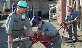 Trades discovery for women; plumbing, students in uniforms and hard hats using plumbing tools and...