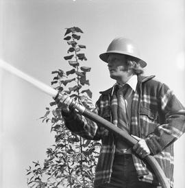 BCIT Programs Forestry Technology ; man wearing a hardhat spraying a water hose [3 of 3]