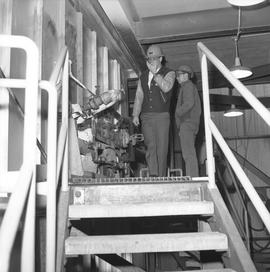 Forestry, Wood fiber BCIT tour, November 26, 1965; two men wearing hard hats looking pipes and va...
