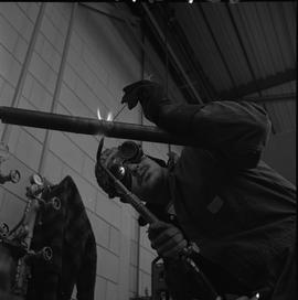 Welding, Terrace, 1968; man wearing protective goggles welding a thin pipe