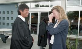 First Nations graduate talking with an instructor (?) [1 of 2 photographs]