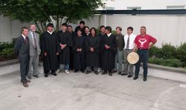 First Nations graduates standing outside in graduation robes with three other staff members [titl...