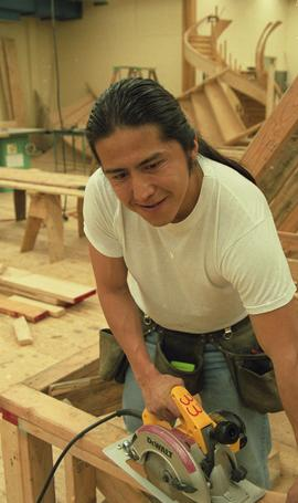 First Nations student wearing a tool belt and using a woodworking tool [13 of 13 photographs]
