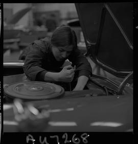 BC Vocational School image of a woman student in the Automotive Mechanics program working on a ve...