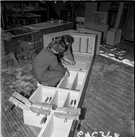 B.C. Vocational School; Carpentry Trades instructor showing a student how to place a door pull on...
