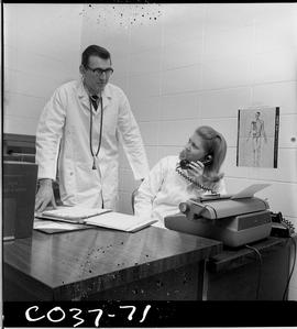 BC Vocational School Commercial Program; medical office with a woman sitting at a desk and a doct...