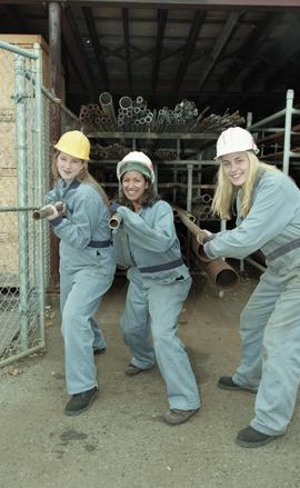 BCIT women in trades; plumbing, students in uniforms and hard hats carrying piping material [2 of...