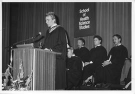 Convocation, January 1987; Dr. J. Basil Peters speaking at a podium, sitting behind him is (left ...