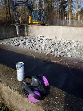 BCIT Lumberman's pool with fence removed, bobcat with jackhammer attachment working, dust protect...